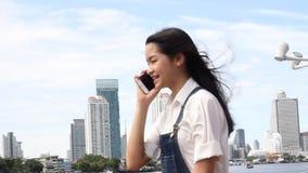 Resposta bonita adolescente da menina do estudante tailandês o telefone e o sorriso vídeos de arquivo