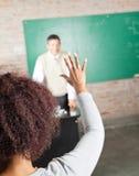 Respuesta de Raising Hand To del estudiante universitario adentro Fotos de archivo