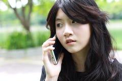 Respuesta hermosa adolescente de la muchacha del estudiante tailandés el teléfono y la sonrisa Imagenes de archivo