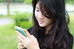 Respuesta hermosa adolescente de la muchacha del estudiante tailandés el teléfono y la sonrisa Imágenes de archivo libres de regalías