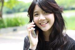 Respuesta hermosa adolescente de la muchacha del estudiante tailandés el teléfono y la sonrisa Foto de archivo