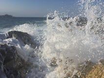 Ressac de mer éclaboussant au-dessus des roches Photographie stock