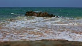Ressac de ressacs de turquoise à la plage contre le ciel bleu