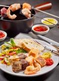 Ressac et fondue de fruits de mer et de viande de gazon Photo stock