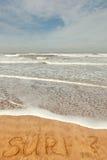 Ressaca da única palavra escrita na areia Fotos de Stock Royalty Free
