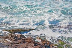 Ressaca pelas rochas Fotos de Stock