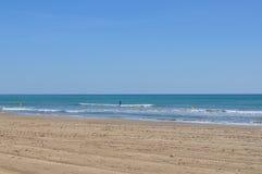 Ressaca praticando na praia Imagem de Stock