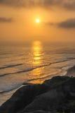 Ressacs au coucher du soleil avec le rivage en pierre et arénacé Images stock