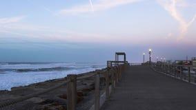 Ressacs se brisant près du rivage, à côté du passage couvert vide illuminé par des réverbères banque de vidéos