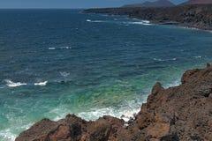 Ressacs se cassant sur la côte rocheuse de la lave durcie avec des cavernes et des cavités Montagnes et volcans sur l'horizon images stock