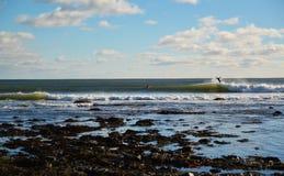 Ressacs se cassant un jour ensoleillé avec des surfers éliminant le varech Photos stock
