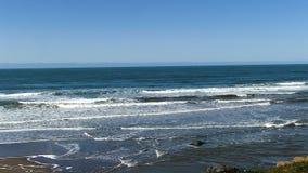 Ressacs sur la plage de sable avec le ciel bleu banque de vidéos
