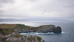 Ressacs sur le rivage rocheux par temps nuageux donnant sur la montagne clips vidéos