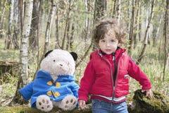 Ressort dans la petite fille de forêt jouant avec un ours de jouet Photographie stock