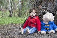 Ressort dans la petite fille de forêt jouant avec un ours de jouet Images libres de droits
