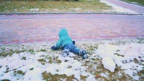 Ressort Tir de Steadicam d'enfant fonctionnant en bas du trottoir, de l'herbe et de la neige de fonte Mouvement lent banque de vidéos