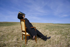 Rest. Business man with a book on his head having a rest on the nature Royalty Free Stock Image