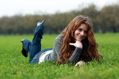 Rest. Beautiful young woman relaxing in the grass Royalty Free Stock Photo