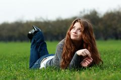 Rest. Beautiful young woman relaxing in the grass Royalty Free Stock Photography