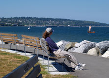 At rest. Young girl resting on a bench watching the sail boats enjoying the sun and view Stock Photo