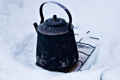At rest. Old sooty kettle stands on the snow Royalty Free Stock Image