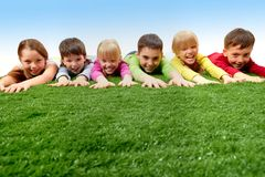 Rest. Group of happy children lying on a grass and stretching their arms Stock Photo