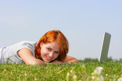 Rest. Young woman with notebook have rest on the grass Royalty Free Stock Image