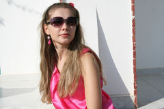 Rest 408. Attractive young girl in a pink dress standing outdoor in front of a wall stock image