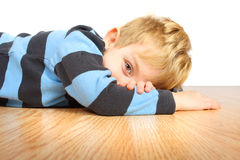 At rest. A young boy rests on a wooden floor royalty free stock photography