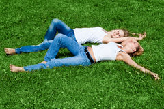 Rest. Two girls have a rest on a green grass Royalty Free Stock Photos