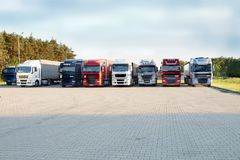 A row of multicolored trucks on a rest stop. Rest area. Other names: motorway service area, travel plaza, rest stop, service area, service station Royalty Free Stock Photo