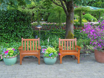 Rest area in the park. Chairs among lush greenery create a rest area in the park Stock Images
