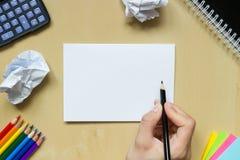 Rest av den skrynkliga papper och handen med en penna på ett skrivbord Fotografering för Bildbyråer