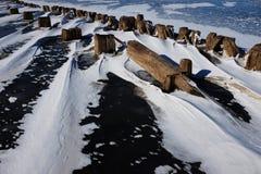 Rest av en träpir i isen på sjön Royaltyfri Fotografi