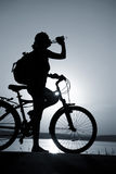 Rest bicycler. Silhouette of the girl on a bicycle, drinking water with beautiful lake near by at sunset Royalty Free Stock Photography