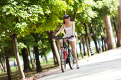 Rest from a bike ride in the park. A young woman takes a rest from a bike ride in the park. She's wearing white sport clothes, cap, her bicycle is red. It's a Stock Photos