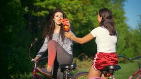 Rest on a bike ride, two female cyclists drink water and talk , sunny summer day. Rest on a bike ride, two female cyclists drink water and talk , against the stock footage