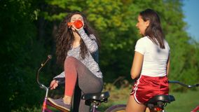 Rest on a bike ride, two female cyclists drink water and talk , sunny summer day. Rest on a bike ride, two female cyclists drink water and talk , against the stock video footage