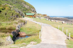 Rest camp at Storms River Mouth. STORMS RIVER MOUTH, SOUTH AFRICA - FEBRUARY 28, 2016:  A mountain stream, camping sites and chalets at the rest camp at Storms Stock Photos