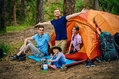Rest in a camping. Friends resting in a camping tent in the forest. Active outdoor recreation royalty free stock photo