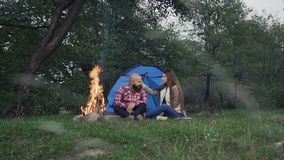 Rest on camping - A man who has a beard and woman with long hair is sitting at the burning fire in a tent town stock video