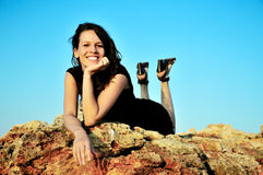 Rest on cliff. Happy brunette girl laying on the cliff at sunset time Royalty Free Stock Images