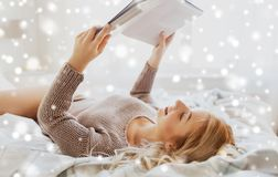 Young woman reading book in bed at home Royalty Free Stock Images