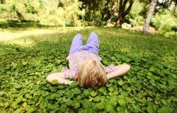 Rest des kleinen Jungen auf der grünen Parkwiese Lizenzfreies Stockfoto