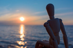Rest in evening. Wooden dummy on the coast in evening Royalty Free Stock Photo