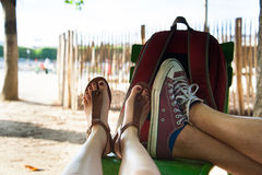 Rest for feet  after walk. Man and Woman relaxing in summer park and sitting on the chair. Young couple enjoy the  summer and have rest for feet  after walk Stock Photography