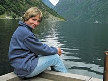 Rest in fjords. Young woman sitting on coast of a fiord Stock Images