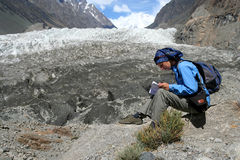 Rest In Front Of The Glaciar. Woman resting and reading a guidebook in front of the glaciar in Karakorum in Pakistan Stock Photo