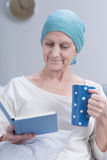 Rest is the key to recovery. Woman after chemotherapy is sitting with book and cup of tea in her hands Stock Photo