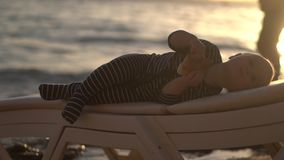Rest of the kings - little baby eat bun in slow motion at sunset. stock footage